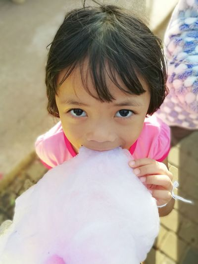 Cute girl eating cotton candy while standing outdoors