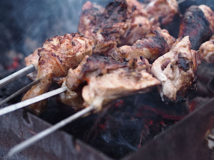 Winter shish kebab fried over an open fire. smoke from fire and steam from hot meat in the cold.