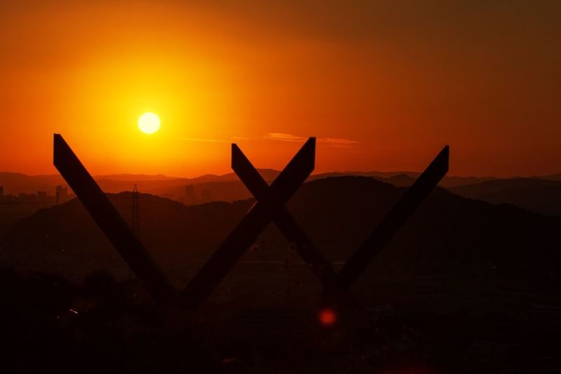 Scenic View Of Mountains Against Orange Sky At Sunset