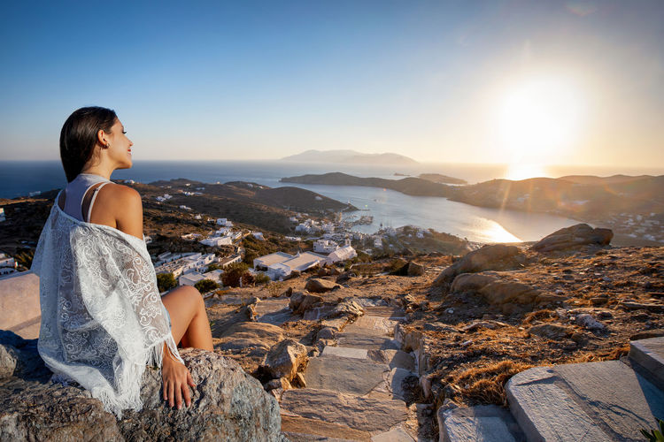 Smiling woman sitting on rock against sky