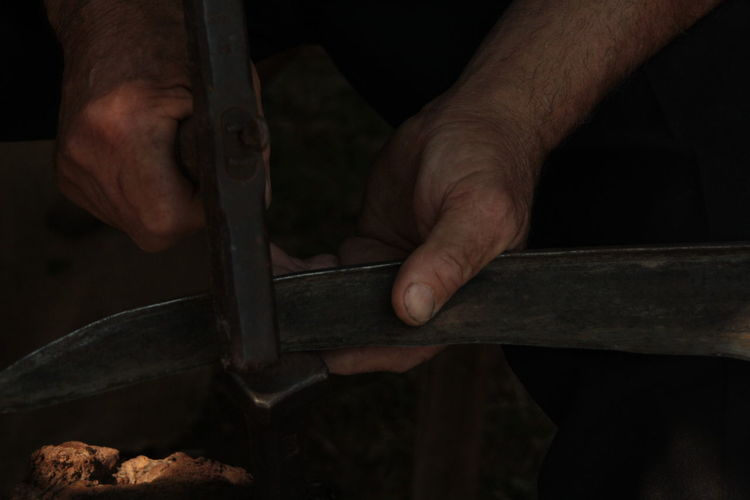 Cropped hand hammering on metal at workshop