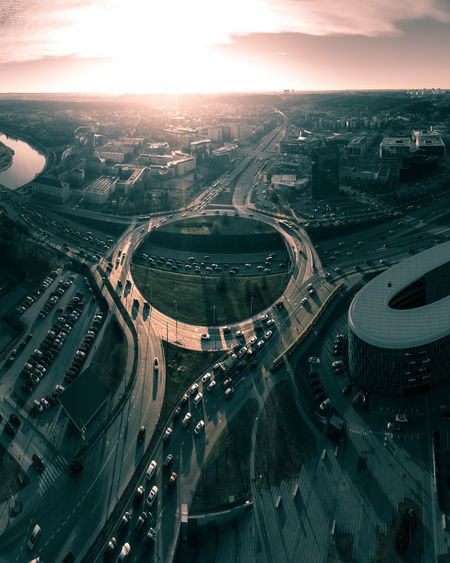 Big city traffic at sunset, roundabout, aerial view High Angle View Transportation City Road Highway Bridge Street Nature Cityscape Multiple Lane Highway Bridge - Man Made Structure Aerial View Overpass Elevated Road Roundabout Vilnius Lithuania Lietuva Traffic Sunset Sunrise Traffic Jam Circle Moody Sky Dramatic