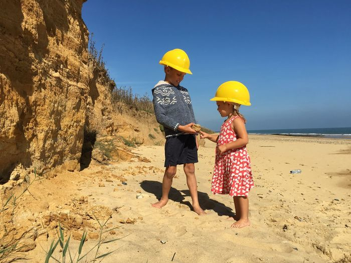 Siblings wearing hardhat while standing on beach