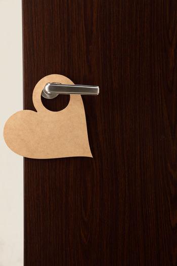 Close-up of heart shape do not enter sign on doorknob