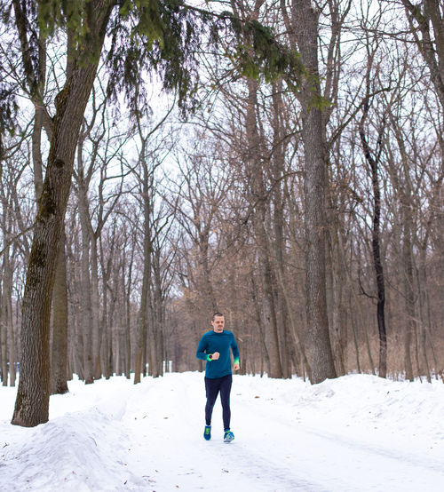 Man running in snow forest in winter. Sportsman runner. Snow Winter Tree Cold Temperature One Person Full Length Plant Lifestyles Land Leisure Activity Nature Real People Day Forest Standing Bare Tree Warm Clothing Beauty In Nature Outdoors Runner Running