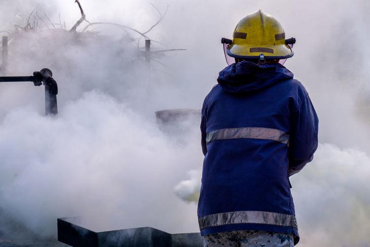Rear view of firefighter spraying firefighting foam