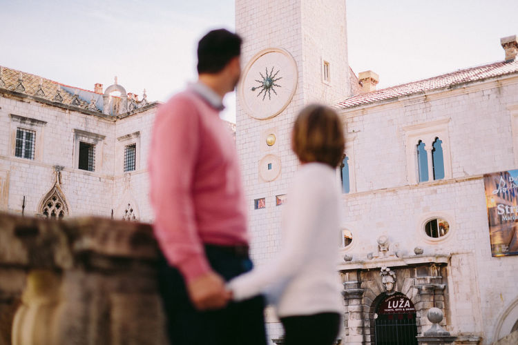 Rear view of couple standing against buildings in city