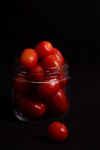 Close-up of tomatoes in glass jar against black background