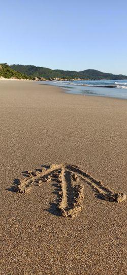 Footprints on sand at beach against clear sky
