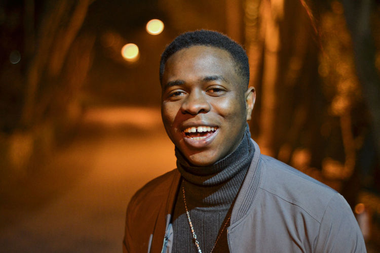 Portrait of laughing young man standing on road at night