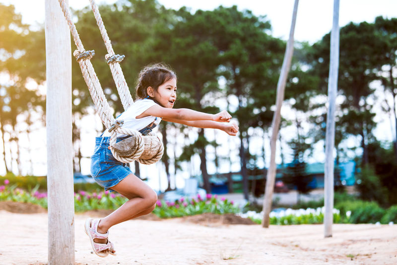Full length side view of girl swinging at playground