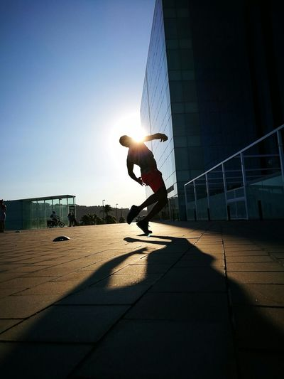 Silhouette men dancing on footpath against sky