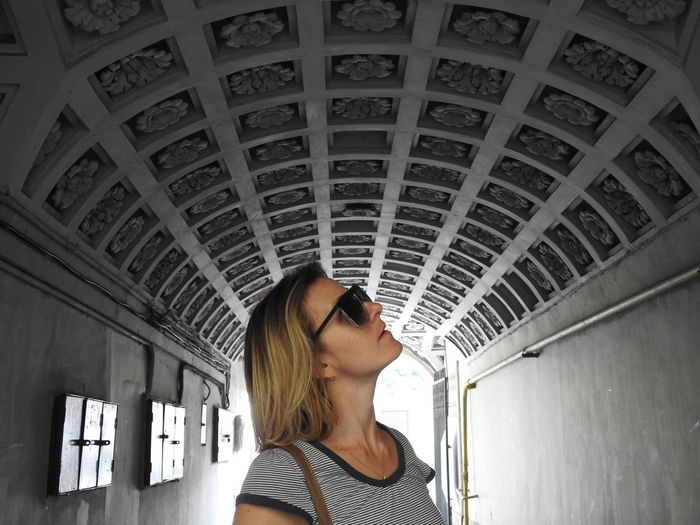 Woman wearing sunglasses while standing in tunnel