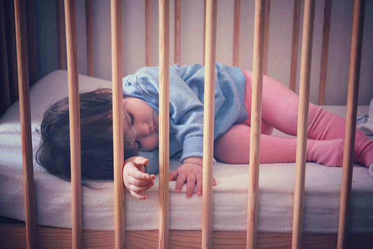 Cute baby girl sleeping in crib at home