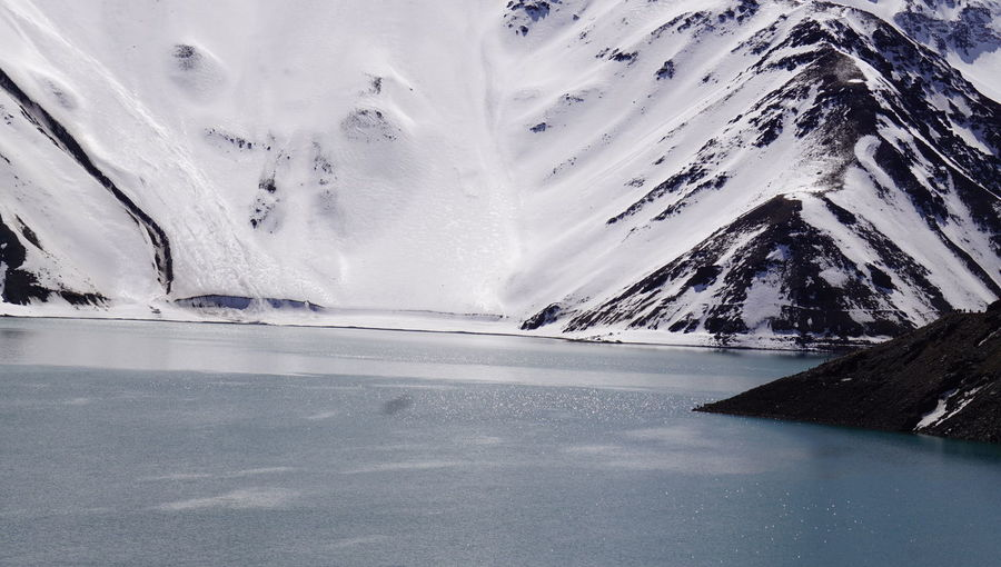 Scenic view of frozen lake by snowcapped mountain