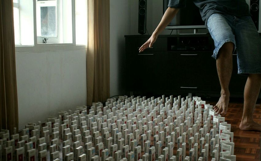Low Section Of Man Balancing On Cigarette Packs At Home