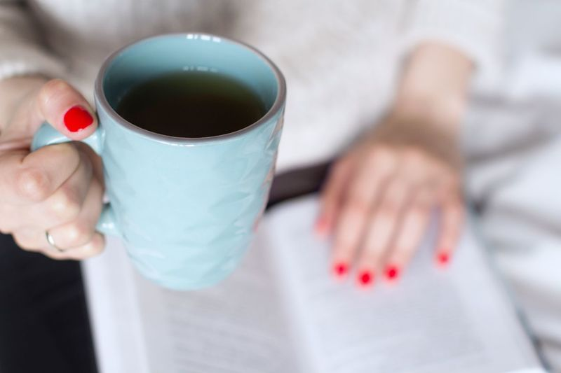 Young woman in beige sweater reading a book on a bed with a cup of tea Storytelling Bedroom Book Hobby Cozy Sweater Red Nail Polish Tea Cup Mug Studying Tea Bedtime Bestsellers Novel Imagination Relaxing Poetry Leisure Activity Literature Learning Reading Open Book  Pages