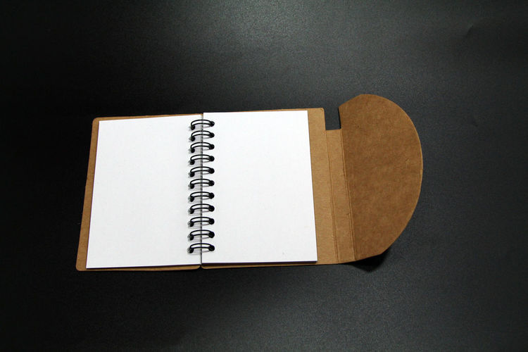 High angle view of open book on table against black background