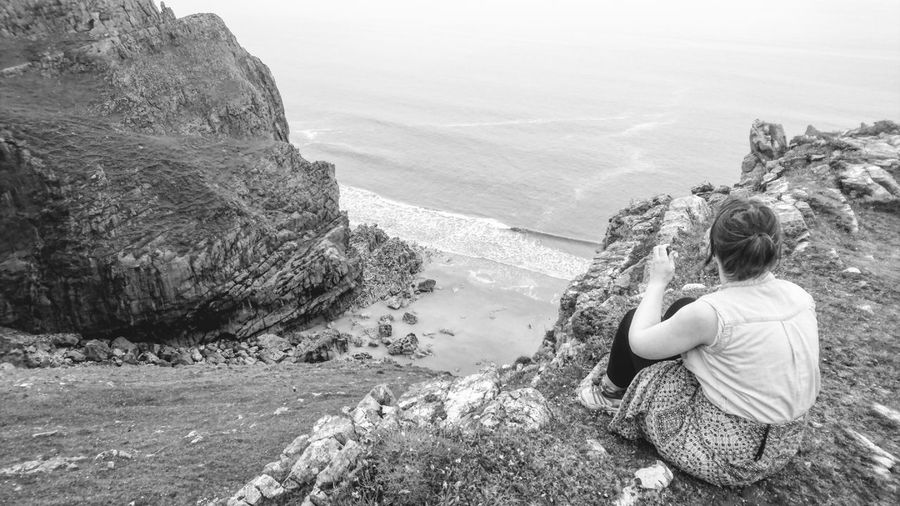 Woman looking at sea while sitting on cliff