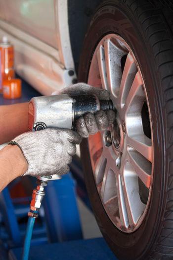 Cropped hands of mechanic repairing wheel