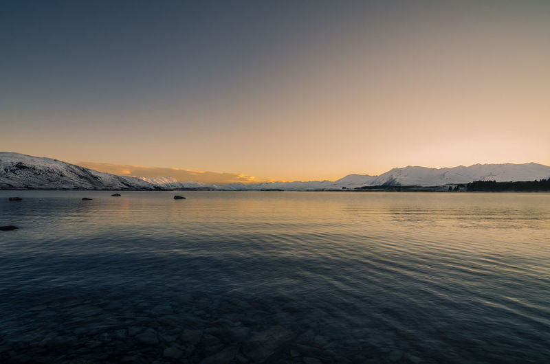 Scenic view of lake tekapo against sky at dawn