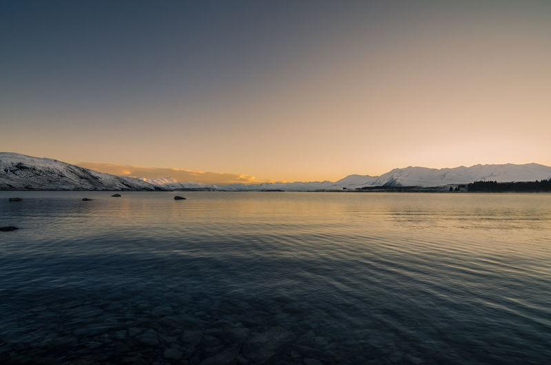 Scenic view of lake tekapo against sky at dawn