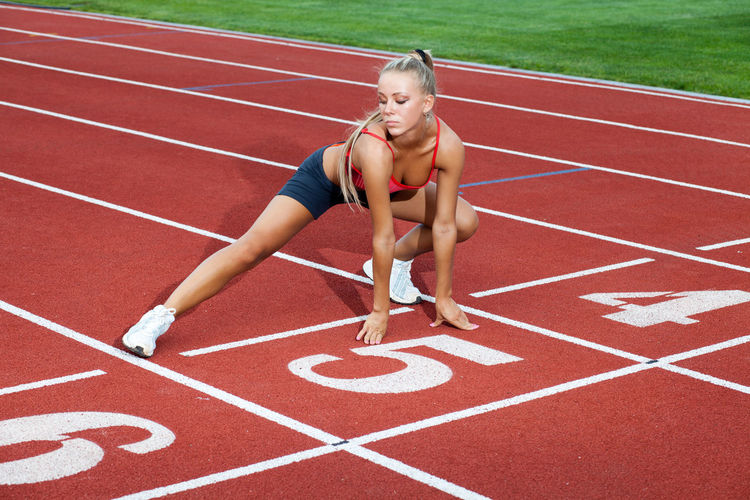 Beautiful woman in a sports suit doing training exercises before running Track And Field Sport Running Track Competition Running Sports Race Young Adult Lifestyles Exercising Sports Track Women One Person Healthy Lifestyle Competitive Sport Adult Athlete Full Length Track And Field Athlete Starting Line Outdoors Track Starting Block