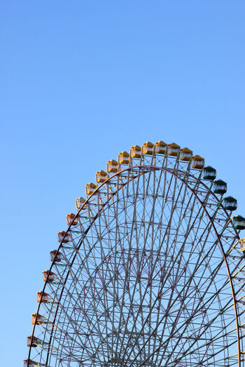 High section of cropped ferris wheel against clear blue sky