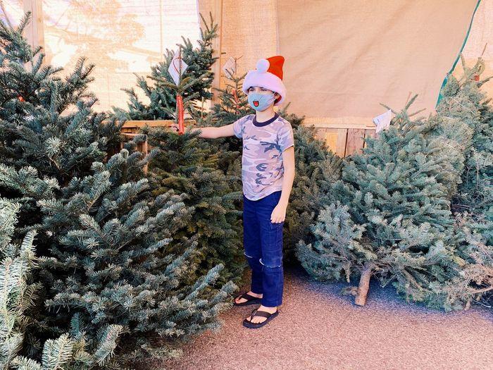 Full length of man standing in christmas tree