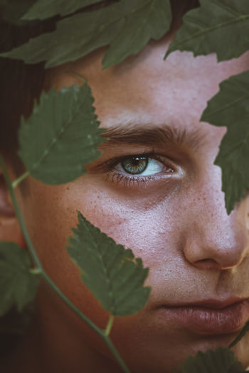 Close-up portrait of boy standing by plants
