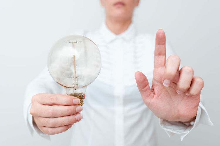 Close-up of hand holding light bulb over white background