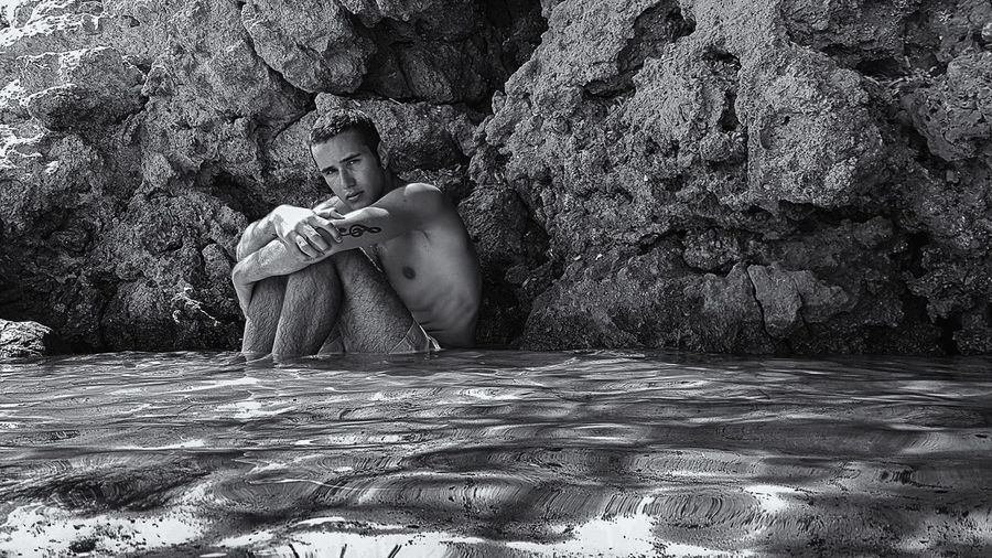 Portrait Of Depressed Young Man Sitting In Sea By Rocks