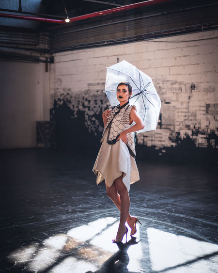 Full length portrait of woman holding umbrella while standing on floor