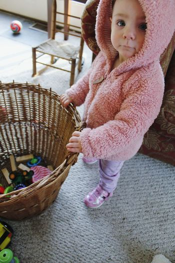 Full length portrait of cute baby girl holding basket with toys at home