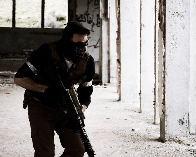 Terrorist with gun standing by wall