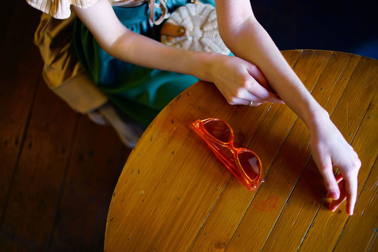 High angle view of woman sitting by wooden table