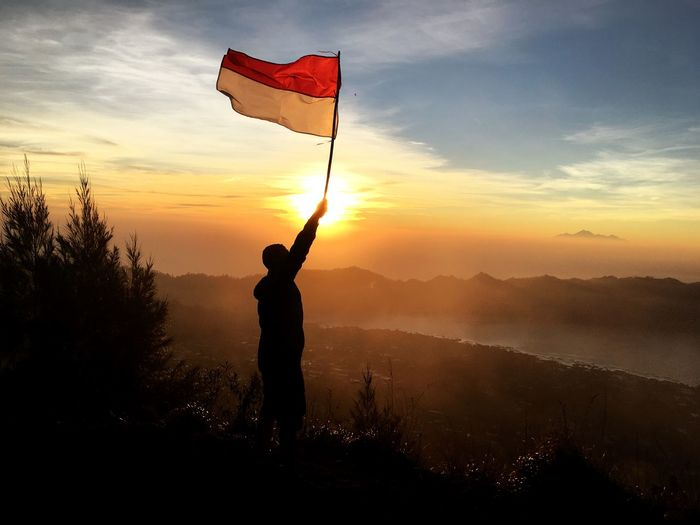 Man holding flag while standing on mountain against sky during sunset