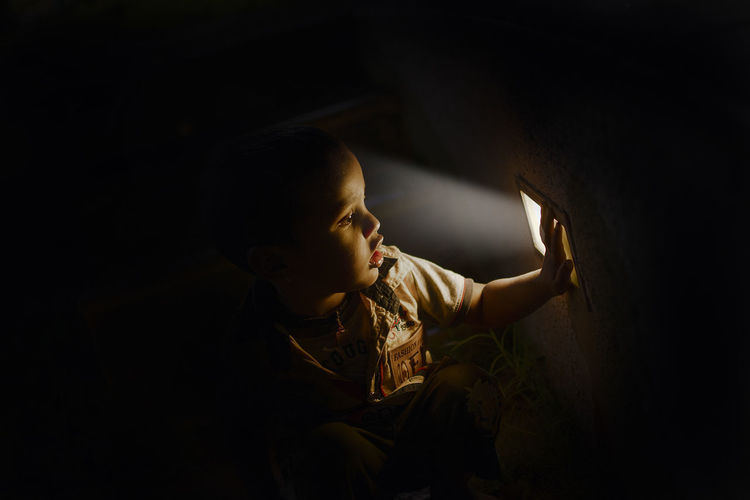 Boy Touching Lighting Equipment While Sitting In Darkroom