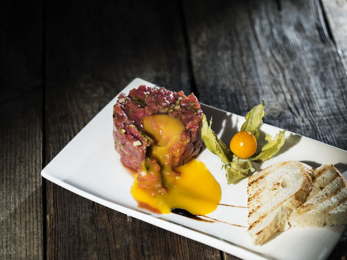 Raw steak tatar with egg yolk Bread Breakfast Close-up Day Egg Food Food And Drink Freshness Healthy Eating Indoors  Indulgence Meat No People Plate Raw Ready-to-eat Serving Size SLICE Steak Table Tatar Wood - Material Yolk