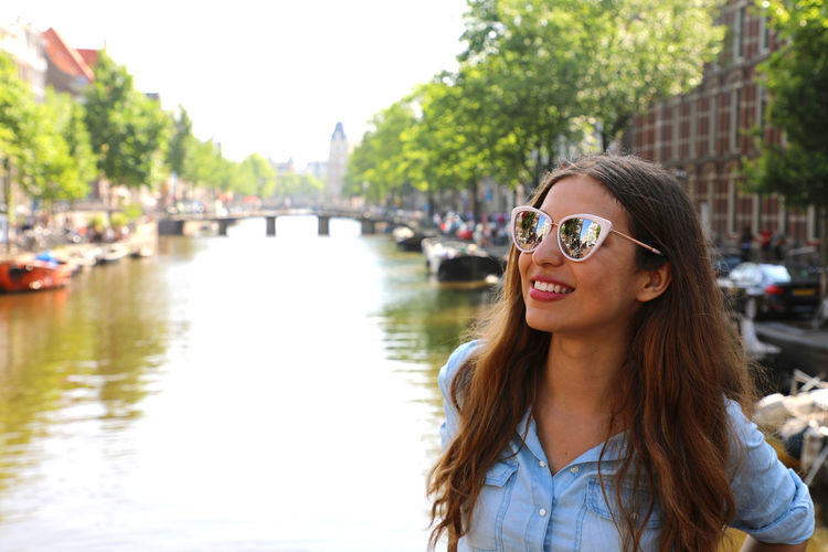 Young woman standing by canal in city