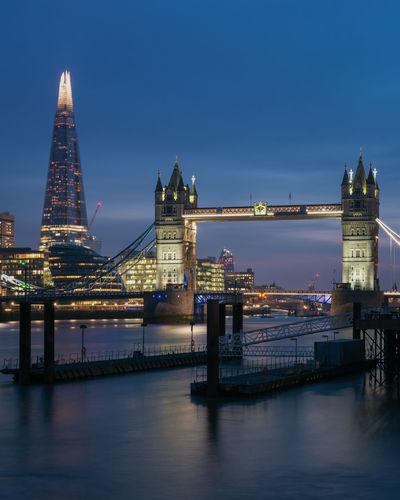 Illuminated tower bridge over river against sky in city