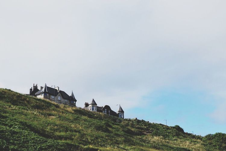 Low angle view of houses on grassy hill against sky