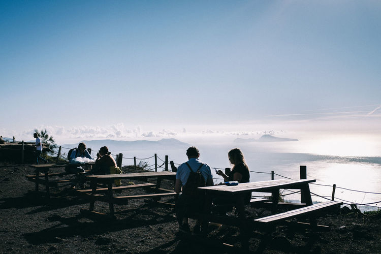 People sitting on bench looking at sea against sky