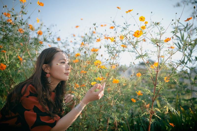 Young woman with flowers on field