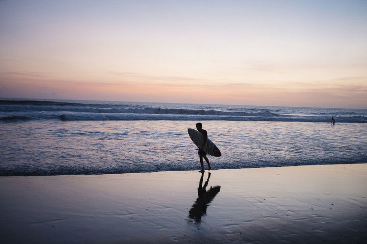 Silhouette Man With Surfboard Walking At Beach Against Sky During Sunset