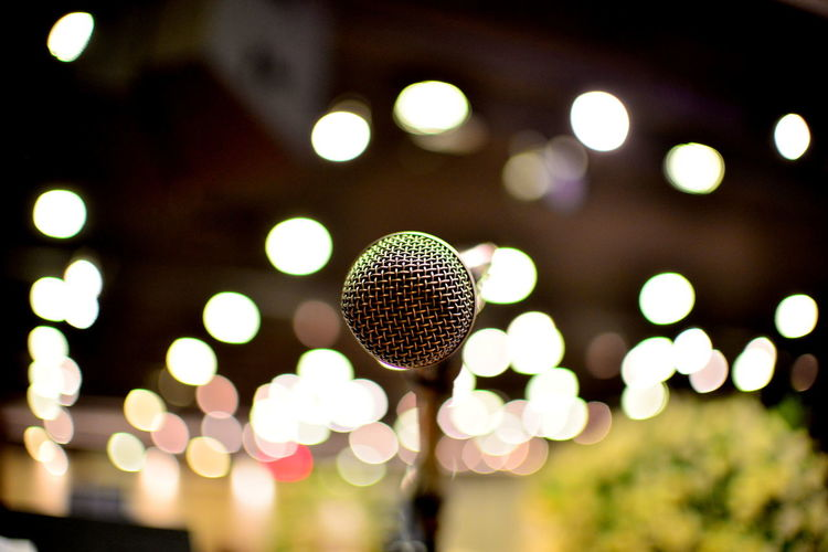Close-up of microphone against illuminated lighting equipment at night