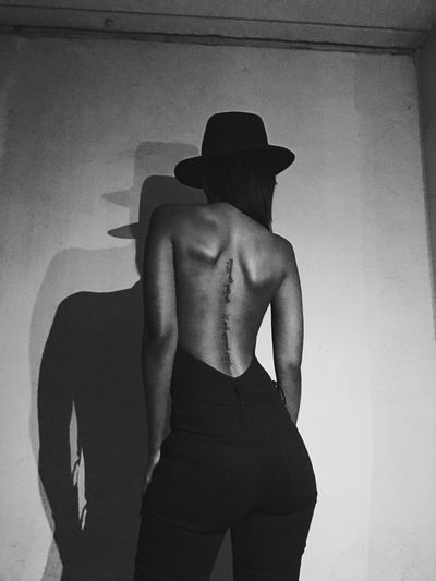 Rear view of shirtless woman standing against wall