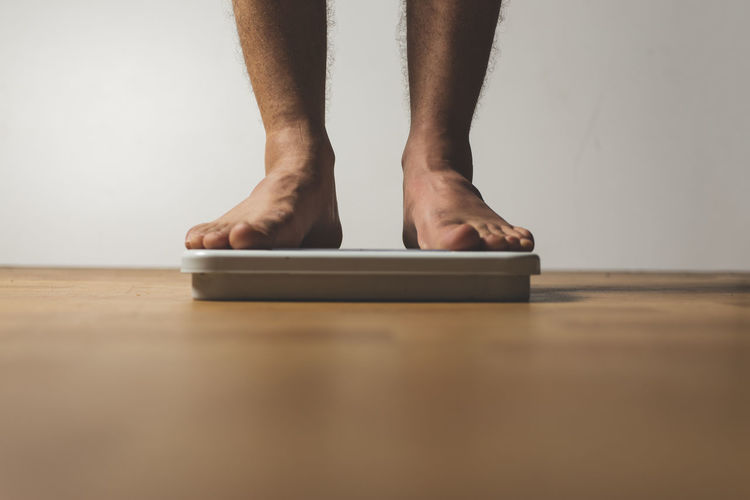 Low section of man standing on weight scale over hardwood floor at home