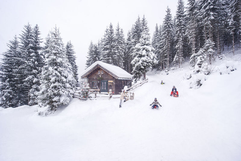 People on snow covered land and houses against sky
