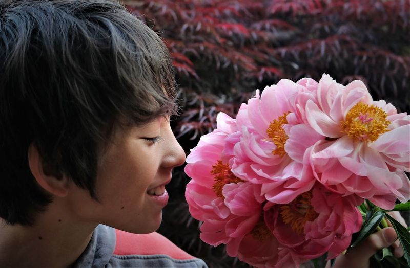 Close-Up Of Smiling Boy Smelling Pink Flowers